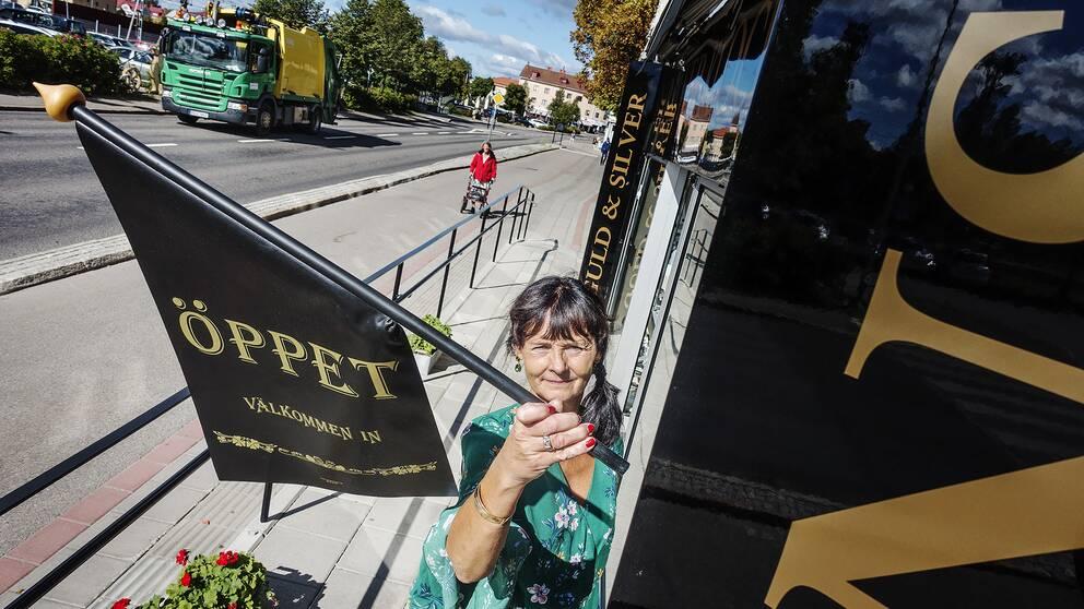 Ninni Nordeen Nyberg, butiksägare i Ljusdal, hänger öppet-flaggan utanför sin butik.