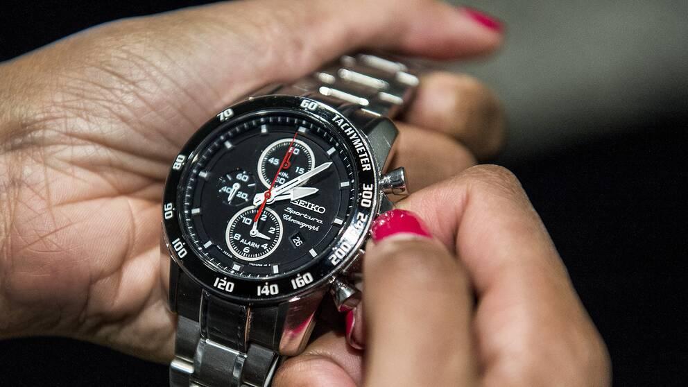 En person ställer om sin klocka.