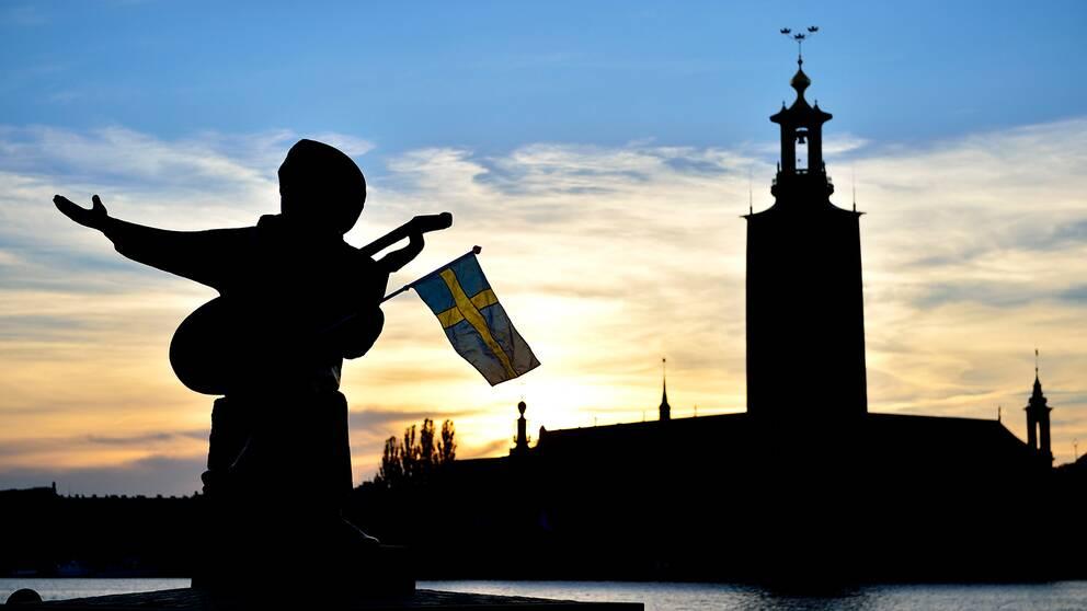 Evert Taube-statyn på Riddarholmen med en svensk flagga i famnen. Stadshuset i bakgrunden.