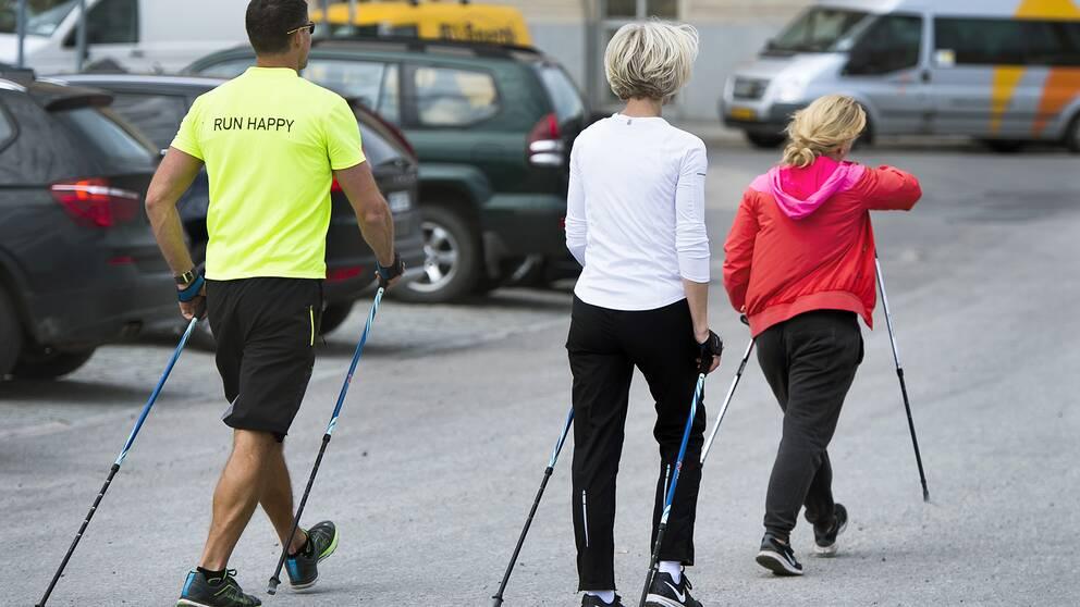 Tre personer går med stavar i förda träningskläder.