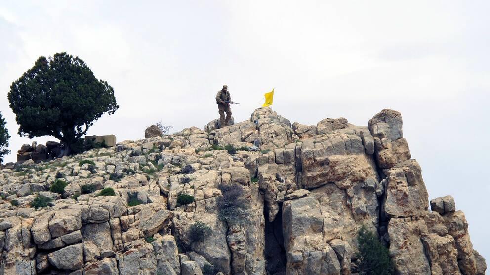 En hizbollahsoldat står på ett berg i Syrien, bredvid honom vajar organisationens flagga.