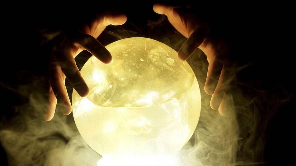 Två händer ovanför en lysande kristallkula omgiven av rök.