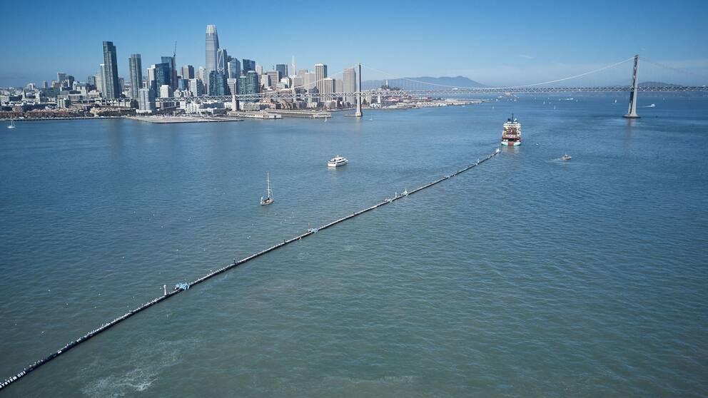 Den 600 meter långa barriären bogseras nu ut till den stora plastsamling finns mellan den amerikanska västkusten och Hawaii. Där ska man börja plocka upp skräpet och frakta det till återvinning.