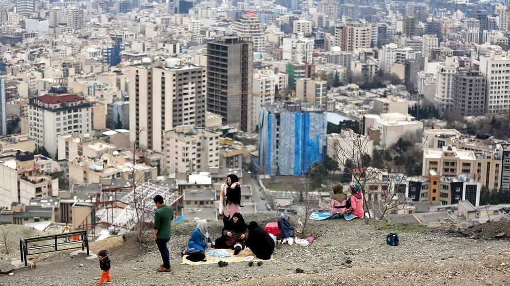 En familj sitter på toppen av en park i Iran som blickar ut över husen.