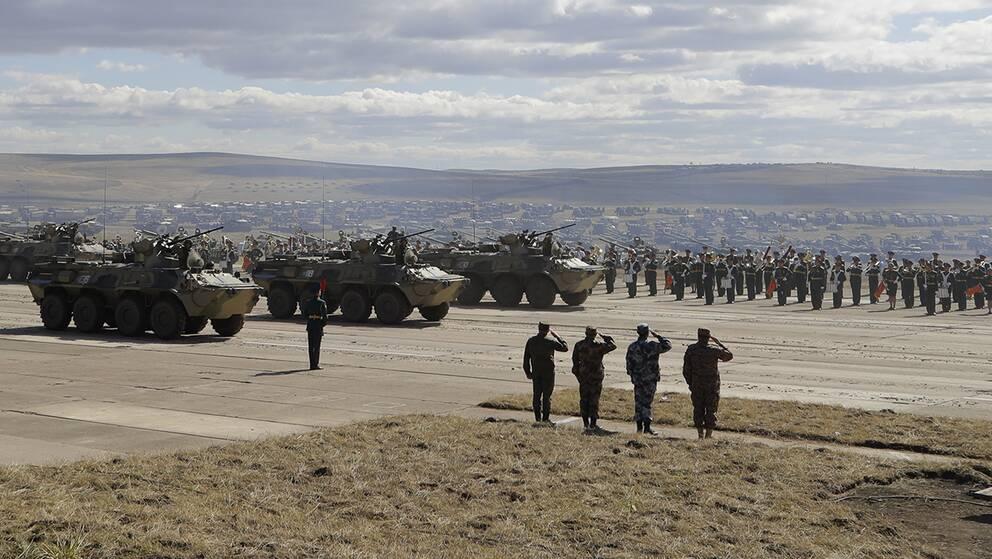 En stor militärövning med stridsvagnar, helikoptrar och infanterister på ett fält.