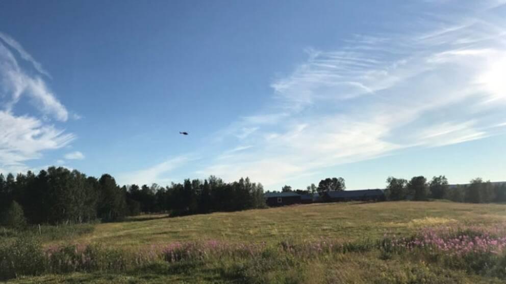 Polishelikopter flyger över äng och ett par hus.