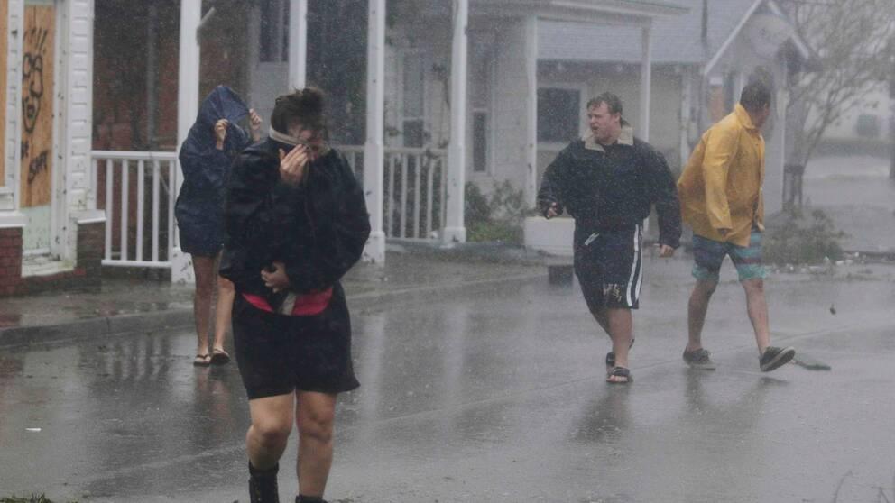 Två kvinnor och två män flyr undan regnet i North Carolina.