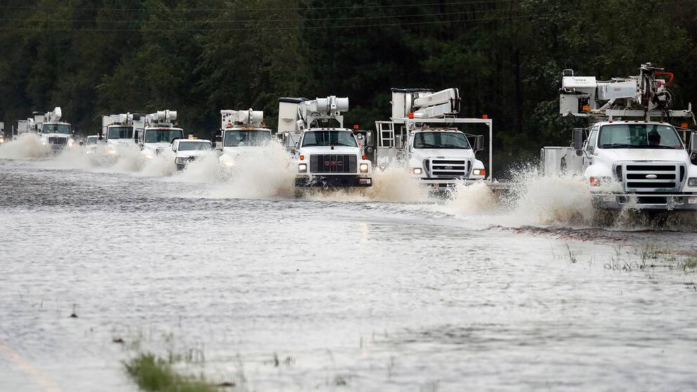 Flera lastbilar kör genom vattenmassorna.