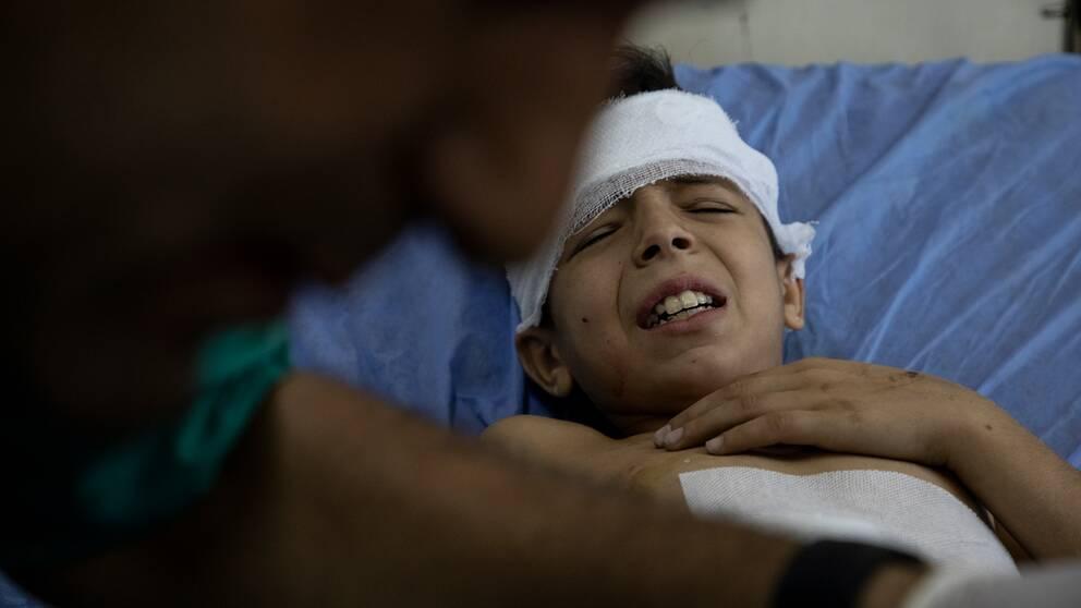 Ett skadar barn i Syrien grinar illa när han undersöks av läkare.
