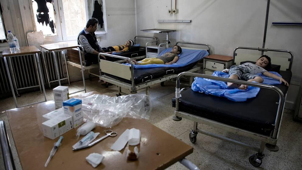 Tre barn ligger på sjukhussängar i Aleppo. En vuxen man vakar över dem.