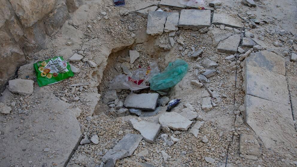 Ett hål i gatan i Aleppo efter en raketattack.