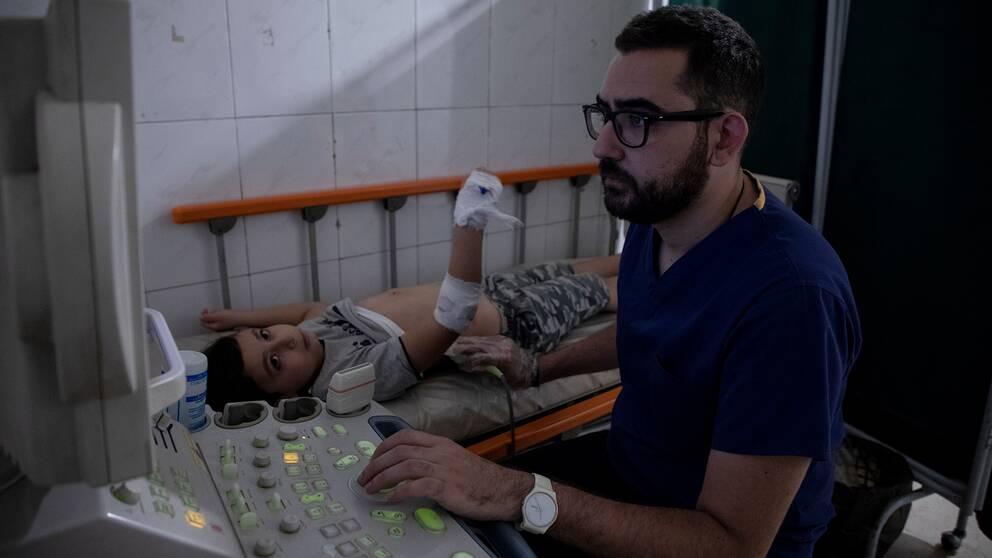 En läkare röntgar en splitterskadad pojkes buk.