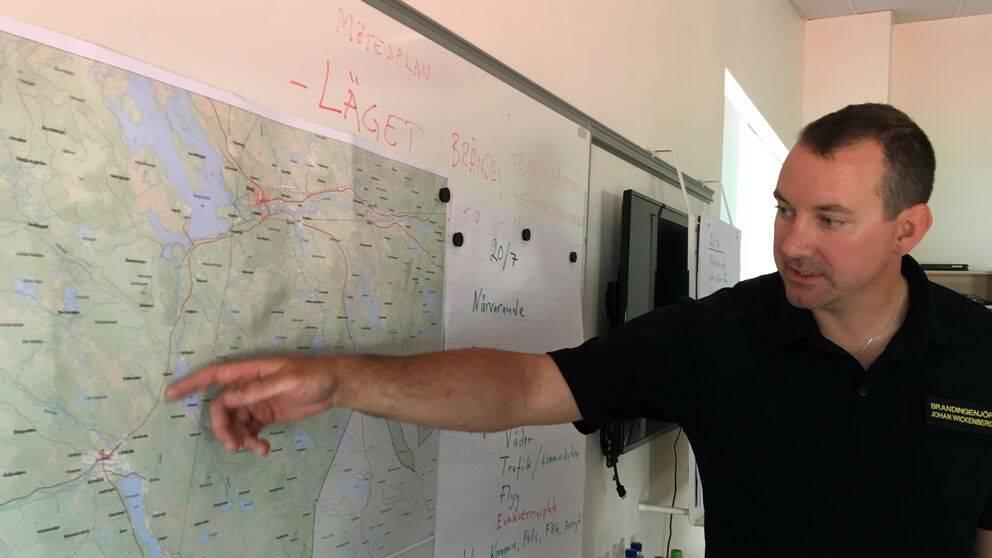 en man pekar på en karta på väggen