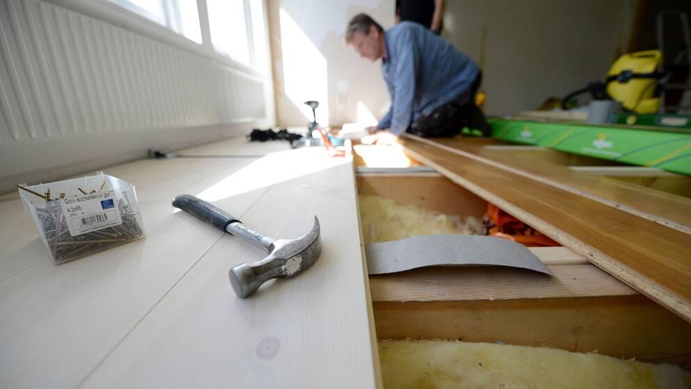 En snickare lägger ett trägolv i en villa. Under golvet syns husets isolering.