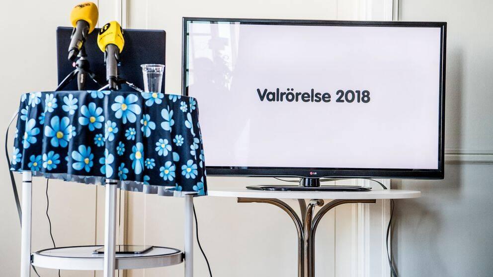 """mikrofoner står på bord med SD-logotyp på duken, en bildskärm med texten """"valrörelse 2018"""")"""