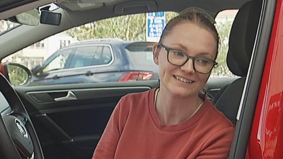 Cecilia Larsson Hall i en röd trafikskolebil.