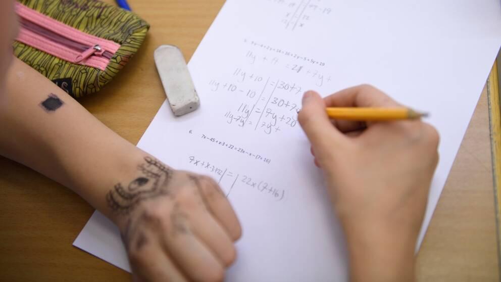 Person skriver på papper med penna.