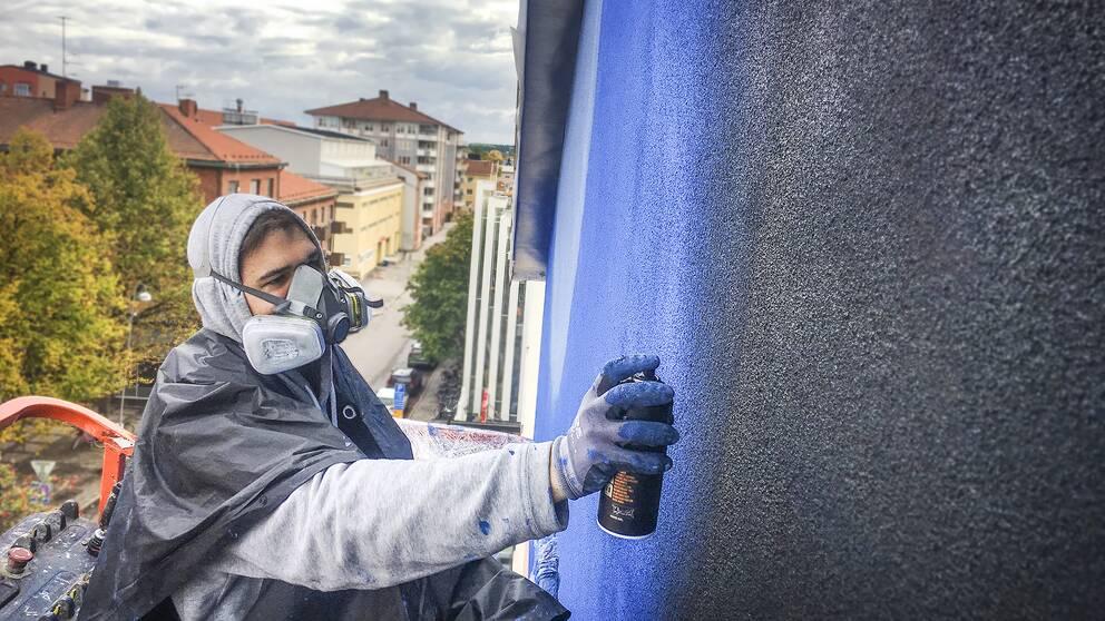 Assistenten Filip arbetar 16 meter upp i en skylift med muralmålningen som tar form på Södermalmstorg.