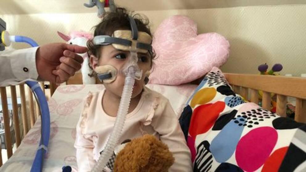 En liten flicka sitter i en spjälsäng och håller i en teddybjörn. Runt hennes ansikte sitter en mask med en slang som går till en maskin.
