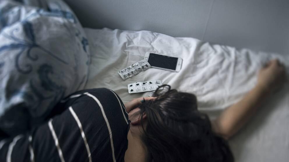 Ung kvinna ligger i sängen med tabletter och mobiltelefon intill huvudet.