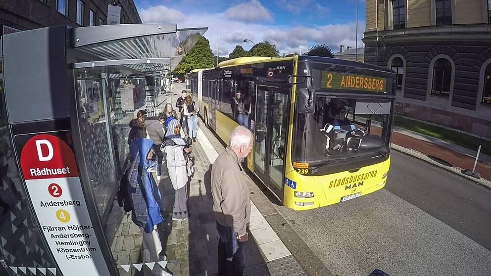 Stadsbuss i Gävle stannar vid hållplats i centrum där passagerare väntar på att stiga på.