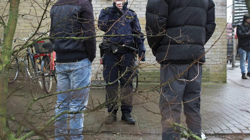 Elever på en skolgård som pratar med en polis.