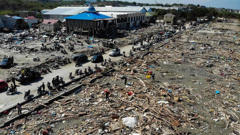 Överlevande söker efter användbara föremål i ruinerna i Palu, Indonesien.
