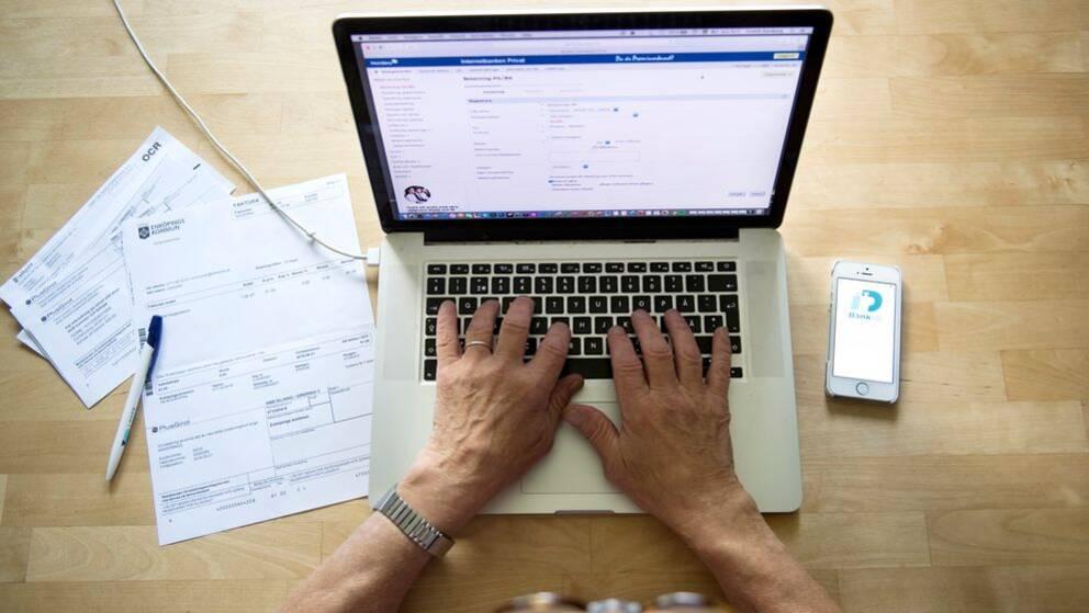 En person vid en dator med räkningar bredvid sig