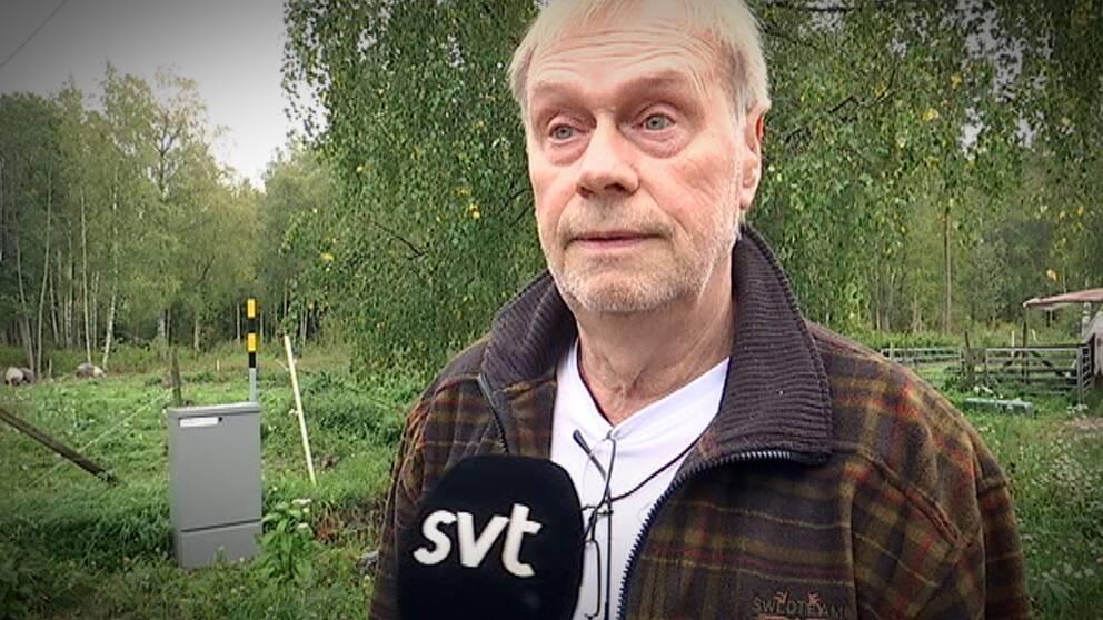 Allan Nykvist står bredvid ett elskåp i grönskan.