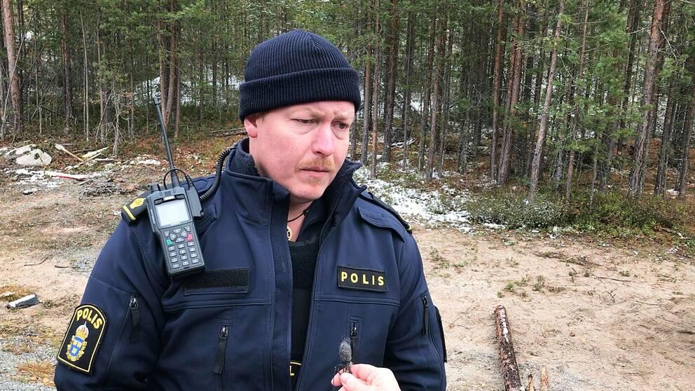 en man i polisuniform fotad på en öppen plats med skog bakom