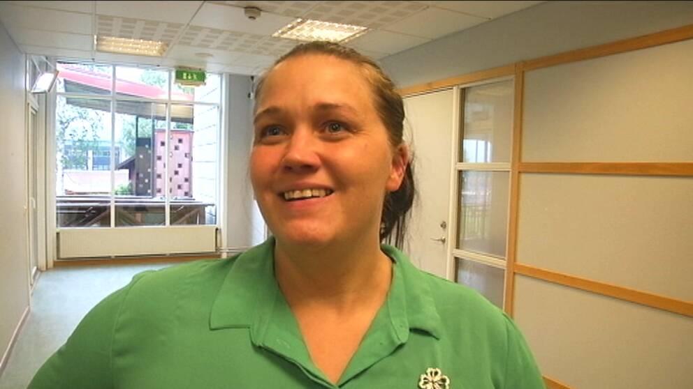 Centerpartiets Annika Andersson har en grön skjorta på sig och ler mot kameran.