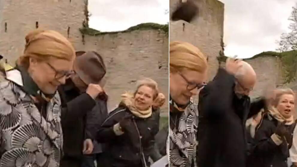 Kung Carl XVI Gustaf som håller i hatten, släpper den – och då blåser den iväg.
