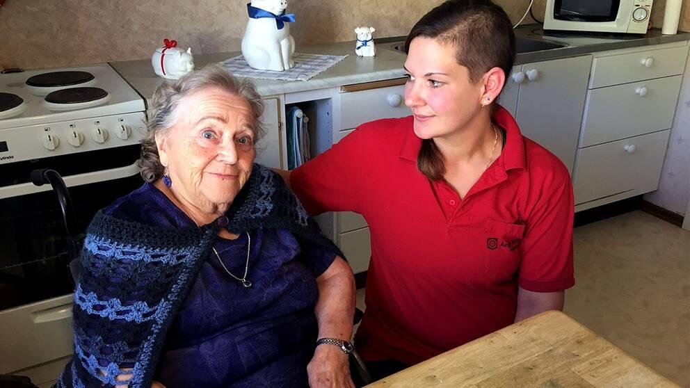 En rullstolsburen äldre dam som sitter vid köksbordet med en kvinnlig personal från hemtjänsten.