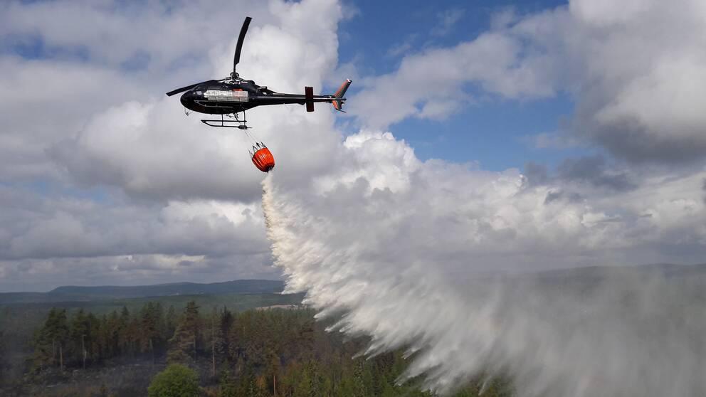flygbild på helikopter som vattenbombar skogen