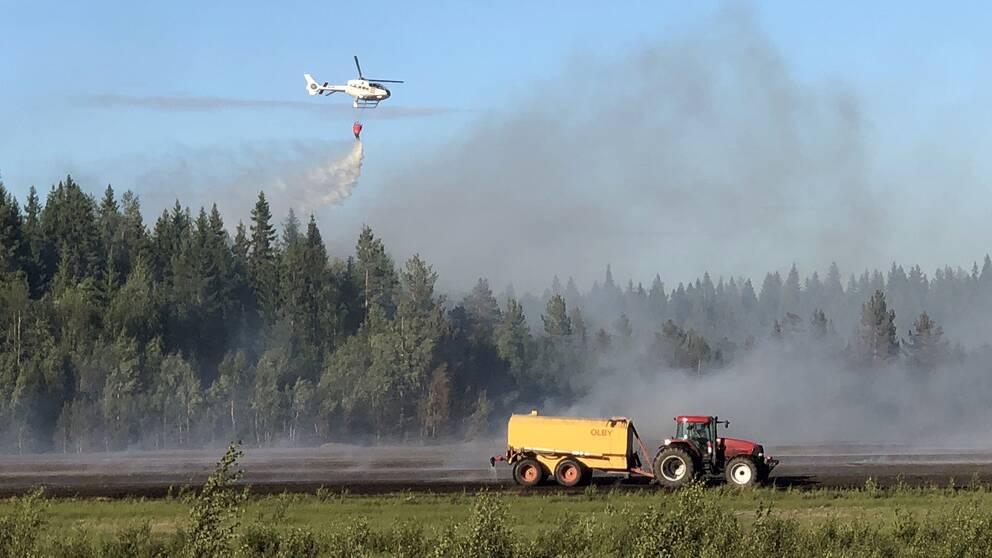 en traktor drar vattentank på åker, helikopter vattenbombar skog i bakgrunden