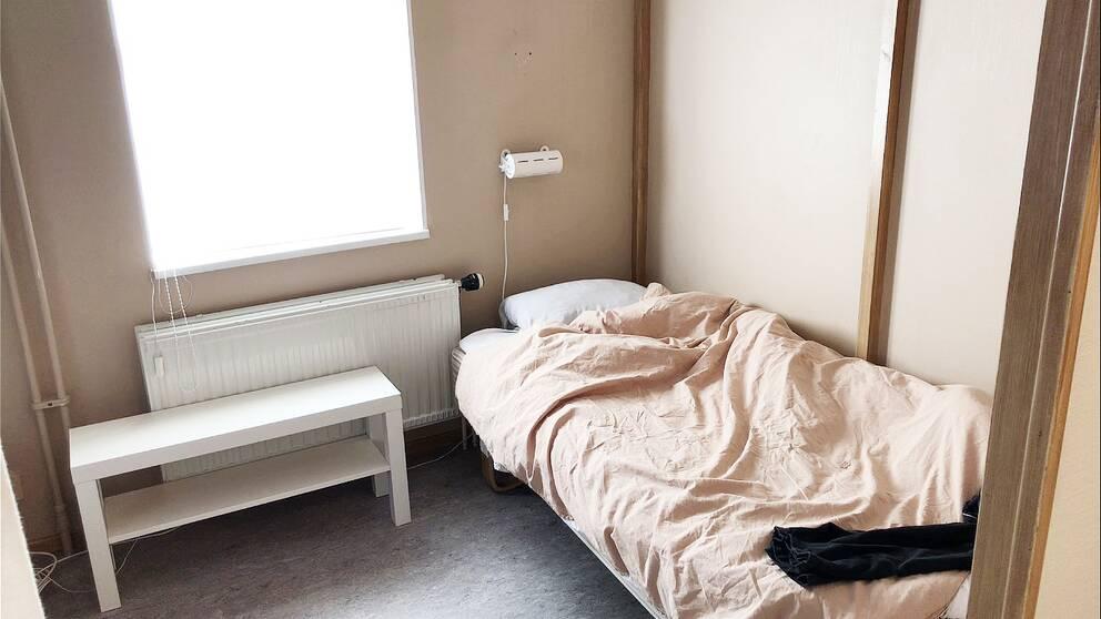 En enkel säng i ett spartanskt inrett rum med ett stort ljust fönster med motljus.