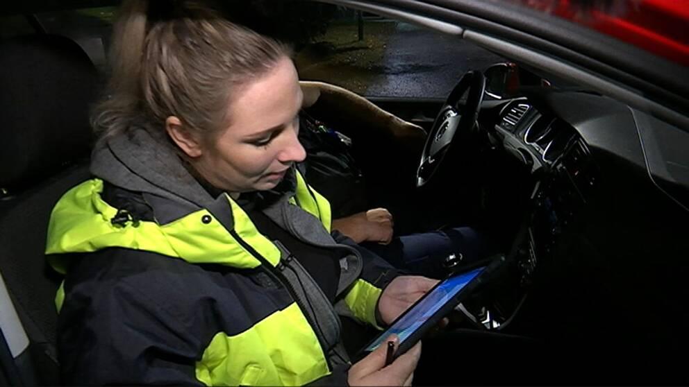 Hemtjänstpersonal som jobbar natten sitter i bilen och tittar på en surfplatta.