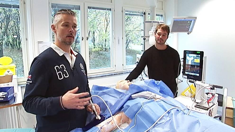 Bild på två personer i sjukhusmiljö som står ovanför en sjukhussäng.