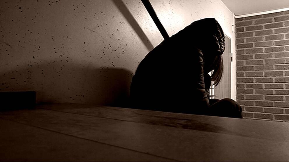 En person sitter i trapphuset och håller händerna för ansiktet.