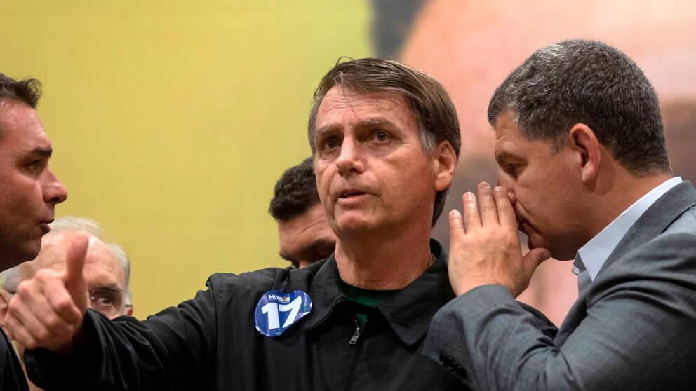 Jair Bolsonaro (mitten) på en presskonferens under valrörelsen. Arkivbild.