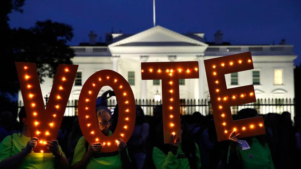 Människor som håller upp bokstäver som bildar ordet vote.