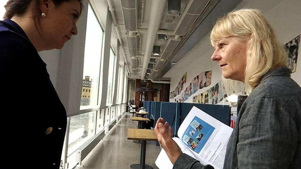 Två personer står och diskuterar, med papper i handen. I bakgrunden en korridor på högskolan.
