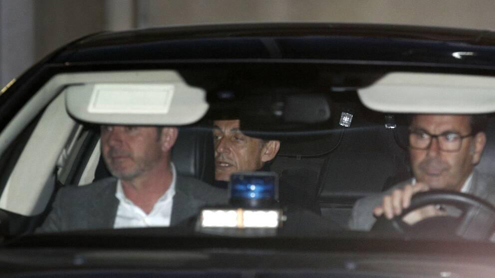 Frankrikes tidigare president Nicolas Sarkozy skymtar i baksätet i en polisbil. Bilden är från i mars i år när han förhördes på en polisstation i Nanterre utanför Paris.