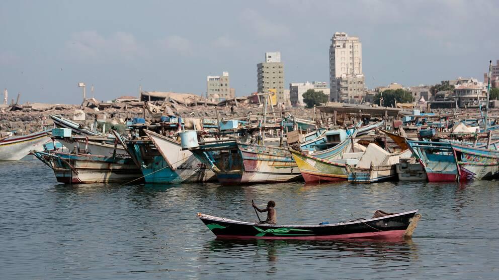 En fiskebåt passerar förstörda byggnader i den viktiga hamnstaden al-Hudaydah (Hodeidah), Jemen
