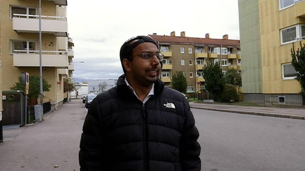Johannes har täckjacka och keps på sned. Han går i ett bostadsområde med trevåningshus. Han ser glad ut och tittar åt sidan.