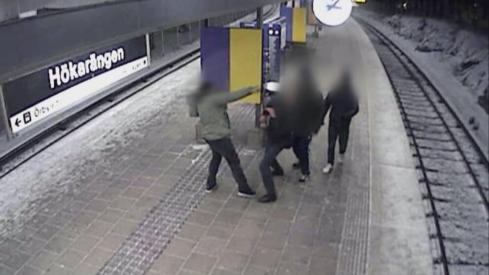 Strax innan knivhugget filmades männen av en övervakningskamera på Hökarängens tunnelbaneperrong. Då överföll de en annan mörkhyad man.