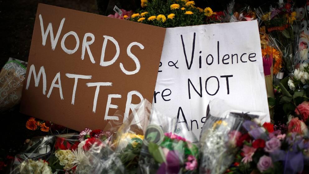 """Plakat med texten """"ord har betydelse"""" bland blommor utanför synagogan Tree of Life i Pittsburgh"""