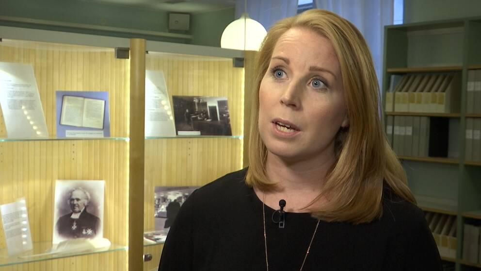 Centerpartiets partiledare Annie Lööf. Bakom henne finns en glasmonter med bilder och en bokhylla med pärmar.