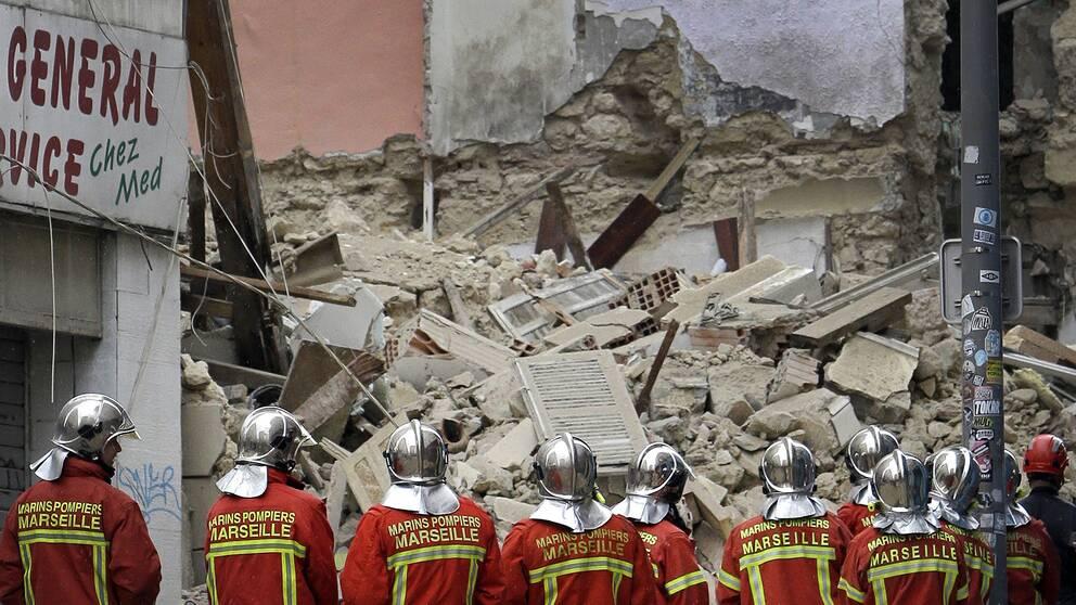 Brandmän på plats vid den adress där husen rasade samman i centrala Marseille under måndagen