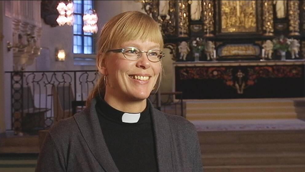 en leende kvinna i prästkläder, i en kyrka